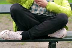 Man sitting cross-legged on the bench and using smartphone - stock footage
