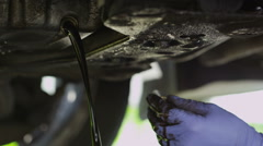 Hands of a mechanic draining oil from a car Stock Footage
