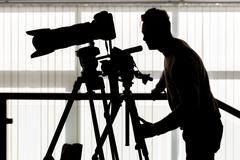Silhouette of photographer and cameraman shot the video on a tripod at the wo Stock Photos