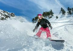 Young woman snowboarder in motion on snowboard in mountains Stock Photos