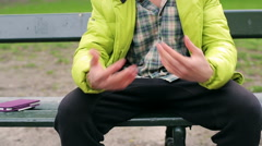 Man talking and gesturing while sitting on the bench Stock Footage