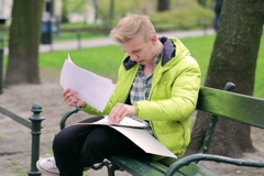 Boy reading papers and smiling to the camera in the park Stock Footage