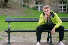 Boy smoking cigarette and looking to the camera in the park - stock footage
