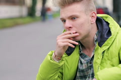 Worried man sitting in the park and smoking cigarette Stock Footage