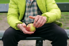Man showing ripe and tasty apple to the camera in the park Stock Footage
