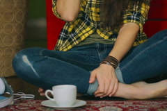 Girl sitting cross-legged on the floor and chatting, steadycam shot - stock footage