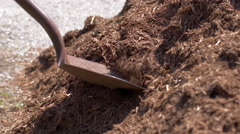 Spade digs out pine mulch from a large pile 4K Stock Footage
