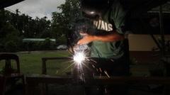 Welder's Helmet Lights up as a Welder welds- PALAU Stock Footage