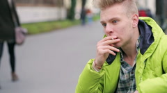 Worried man sitting in the park and smoking cigarette - stock footage