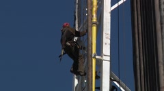 Stock Video Footage of Drilling Rig Worker Climing Derrick with Fall Protection