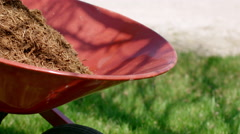 Detail of garden mulch being emptied from barrow 4K - stock footage