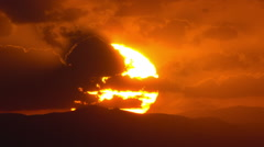 Huge flaming sun rising behind a mountain disappears into clouds  telephoto 30p Stock Footage
