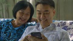 Asian senier woman and asian man using smart phone together Arkistovideo