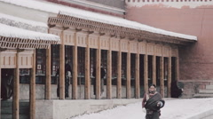 Snow falls as pilgrims circumambulate the Kora path at Labrang Monastery Stock Footage