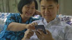 Asian senior woman and Asian man using smart phone together, slow motion Arkistovideo