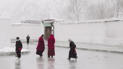 Buddhist monks and pilgrims are covered in snow at Labrang Monastery Stock Footage