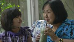 Asian Grandmother with her granddaughter drinking apple juice together Stock Footage