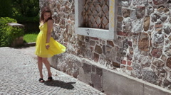 Young attractive woman in yellow dress happily spinning around. Stock Footage