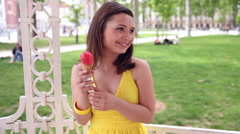 Attractive young woman licking strawberry ice cream in a park and laughing shyly Stock Footage
