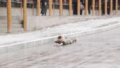 Snow falls as Tibetan Buddhist prostrates herself at the Labrang Monastery Stock Footage