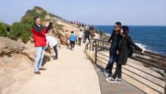 Chinese tourists taking photos at Yehliu Geopark Stock Footage