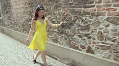 Young attractive woman in yellow dress happily walking by the brick wall Stock Footage
