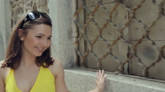 Young attractive woman in yellow dress happily walking by the brick wall. Close Stock Footage