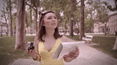 Steadicam shot of cute female tourist walking through a park and taking pictures Stock Footage