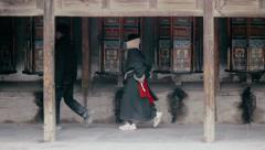 Tibetan Buddhists spin prayer wheels at the Labrang Monastery - stock footage