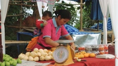 Woman sells vegetables at the market at Doi Mon Jam Royal Agricultural Station. Stock Footage