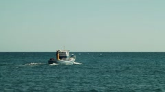 Sailor fisherman on a small motor boat decreas?? on horizont Stock Footage