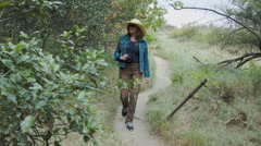 WOMAN WITH A CAMERA WALKS A HILLY, GRASSY PATH Stock Footage