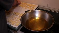 Male throws pierogies into hot oil Stock Footage