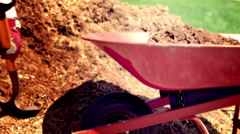 Sunshine tint on barrow being filled with garden mulch 4K - stock footage