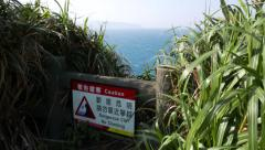Sign and dangerous cliff, looking down risky from very high crag - stock footage