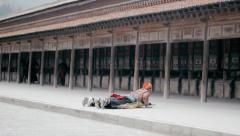 Tibetan Buddhists prostrate themselves as they perform Kora at Labrang Monastery Stock Footage