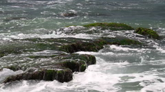 Turquoise rolling wave slamming on the rocks . Stock Footage