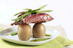 Pork ribs with potatoes, string beans and snow peas - stock photo