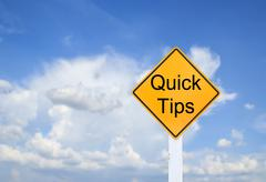 Road sign indicating Quick Tips on blurred sky background - stock photo