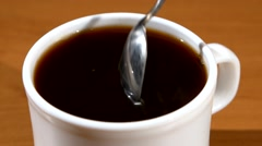 Spoon pouring sugar into a cup of coffee, wood background Stock Footage