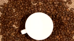 White cup of coffee stands on brown beans, sacking, rotation, close up Stock Footage