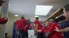 4K Excited American footballers celebrate a victory by lifting coach in the air - stock footage