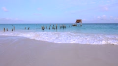 Batered dock taking surf on beautiful Caribbean beach at dusk Stock Footage