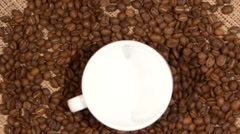 White cup of coffee stands on brown beans, sacking, rotation Stock Footage