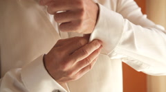 Man Attaches Cuff Button To White Shirt - stock footage