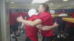 4K Excited American football team celebrate a victory in locker room after game - stock footage