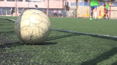 The ball is in foreground at stadium where children play soccer Stock Footage