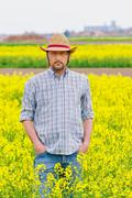 Farmer Standing in Oilseed Rapeseed Cultivated Agricultural Field Kuvituskuvat