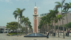 Hong Kong - Tsim Sha Tsui Clock Tower Tourists and Jogger 1 Stock Footage