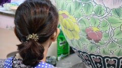 Thai woman drawing and painting glazed water jar Stock Footage